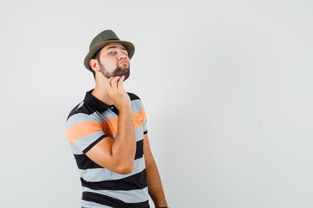 Junger mann im t-shirt, hut, der seine gesichtshaut durch berühren des bartes überprüft und elegant, vorderansicht schaut. Kostenlose Fotos