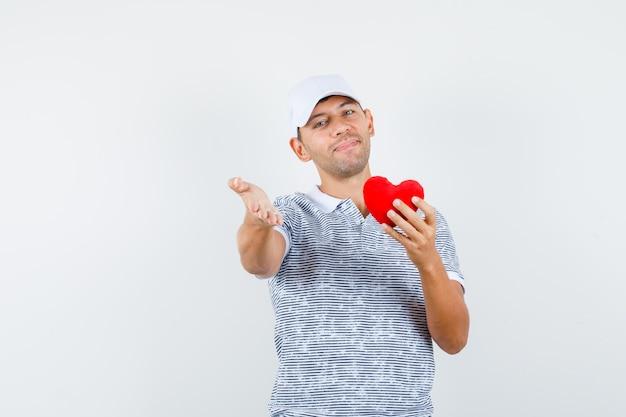 Junger mann im t-shirt und in der kappe, die rotes herz halten, hand ausstrecken und fröhlich schauen Kostenlose Fotos