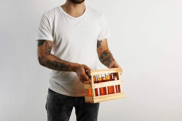Junger mann im weißen baumwoll-t-shirt mit tätowierungen, die eine kiste des handwerklichen bieres lokalisiert auf weiß halten Kostenlose Fotos