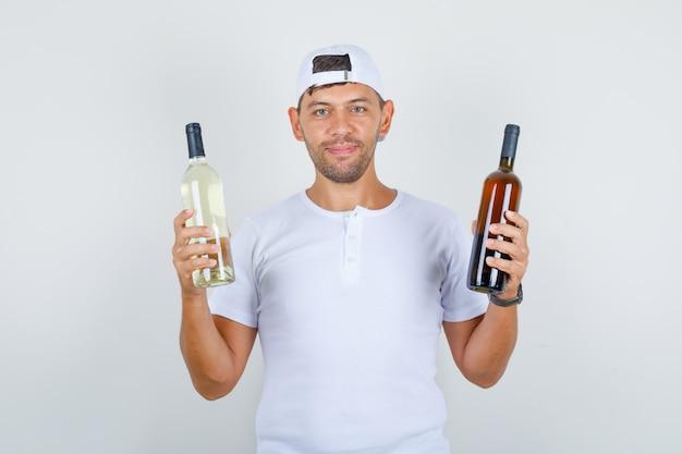 Junger mann im weißen t-shirt, kappe, die flaschen der alkoholischen getränke hält und glücklich schaut, vorderansicht. Kostenlose Fotos