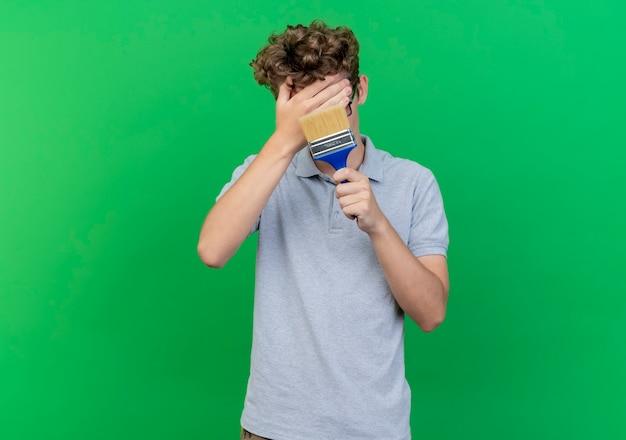 Junger mann in den schwarzen gläsern, die graues poloshirt tragen, das pinselabdeckungsgesicht mit einer hand hält, die verwirrt über grüner wand steht Kostenlose Fotos