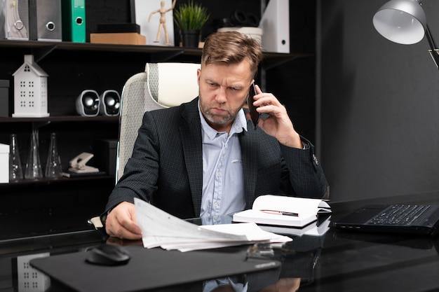 Junger mann in der geschäftskleidung, die am computertisch mit telefon und dokumenten arbeitet Premium Fotos