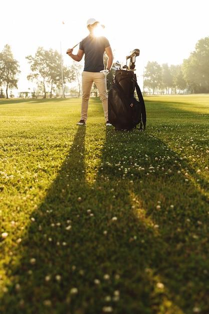 Junger mann in der kappe, die golfschläger hält Kostenlose Fotos