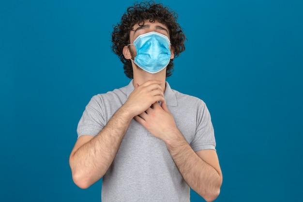 Junger mann in der medizinischen schutzmaske hält hände an seinem hals wegen halsschmerzen über isoliertem blauem hintergrund Kostenlose Fotos