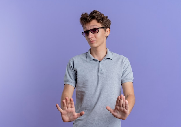 Junger mann in der schwarzen brille, die graues poloshirt trägt, das stoppschild hält, das hände heraushält, wie das erzählen nicht näher kommt, das über der blauen wand steht Kostenlose Fotos