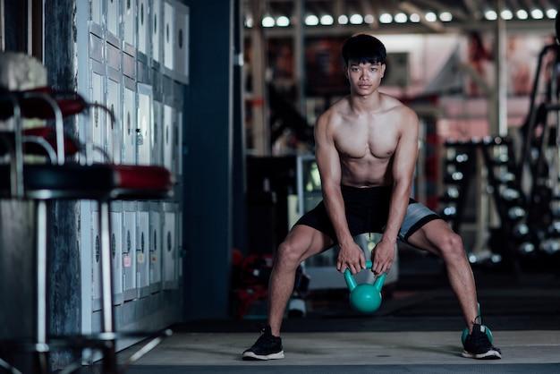 Junger mann in der sportkleidung eine übungsklasse in einer turnhalle Kostenlose Fotos