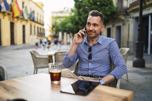 Junger mann in einem formellen outfit, das in einem straßencafé sitzt, das am telefon spricht Kostenlose Fotos