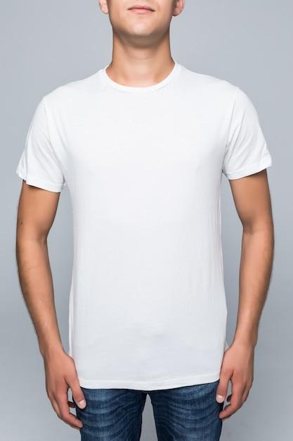 Junger mann in einem lässigen stil kleidet weißes t-shirt und blaue jeans auf weiß Kostenlose Fotos