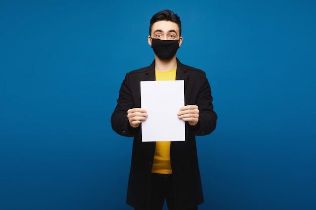 Junger mann in einem schwarzen mantel und in der schwarzen schutzmaske, die mit einem leeren blatt papier am blauen hintergrund, promotionskonzept aufwirft. gesundheitskonzept Premium Fotos