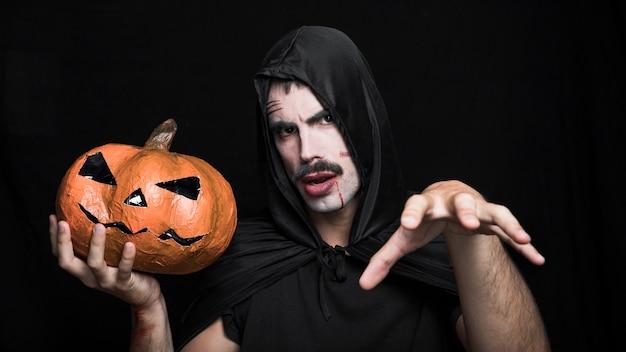 Junger mann in halloween-kostüm, das mit jack o'lantern aufwirft Kostenlose Fotos
