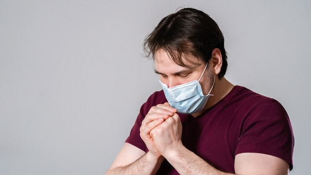 Junger mann in maske, betend um erlösung und schutz vor gefährlichem virus. Premium Fotos