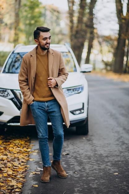 Junger mann in waldtragendem mantel durch das auto Kostenlose Fotos