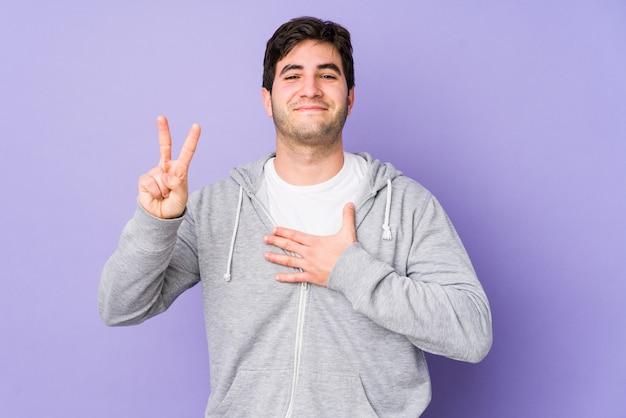 Junger mann isoliert auf purpur, der einen eid leistet und hand auf brust legt. Premium Fotos