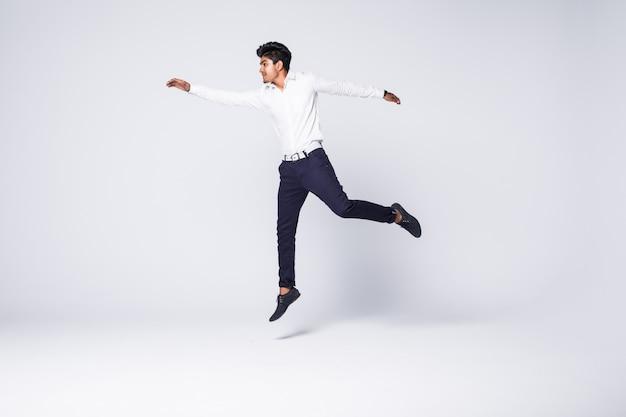 Junger mann jubelt und springt über weiße wand Kostenlose Fotos