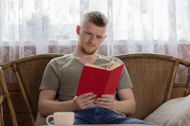 Junger mann konzentrierte sich auf das lesen des buches mit roter abdeckung auf weidenbank im ländlichen holzhaus Premium Fotos