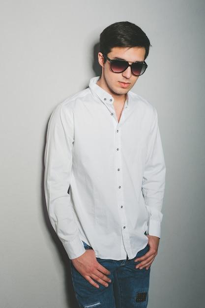 Junger mann kurz gesagt und weißes hemd lächelt, stehend nahe der wand mit gläsern Premium Fotos