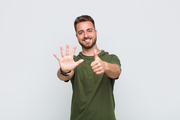 Junger mann lächelt und sieht freundlich aus, zeigt nummer sechs oder sechste mit der hand nach vorne, countdown Premium Fotos