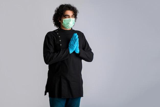 Junger mann macht namaste wegen ausbruch von covid-19. neue begrüßung, um die ausbreitung von coronavirus zu vermeiden, anstatt mit einer umarmung oder einem händedruck zu begrüßen. yoga-praxis für das geistige gleichgewicht. Premium Fotos