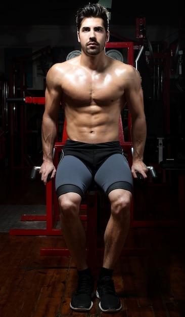 Junger mann macht schwere kraft übung in der turnhalle. Kostenlose Fotos