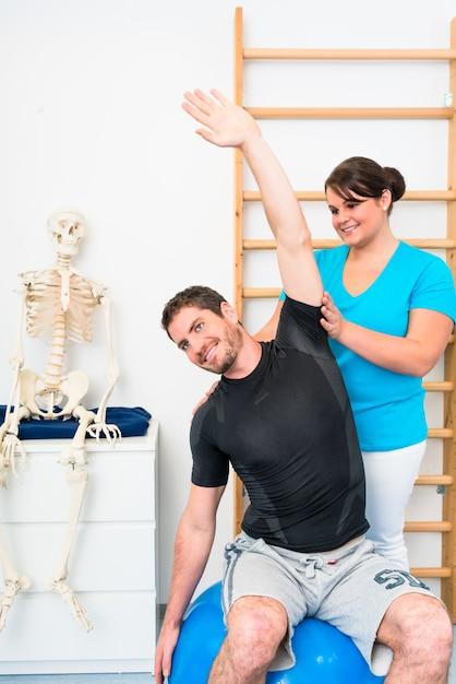 Junger mann macht übungen mit physiotherapeuten Premium Fotos