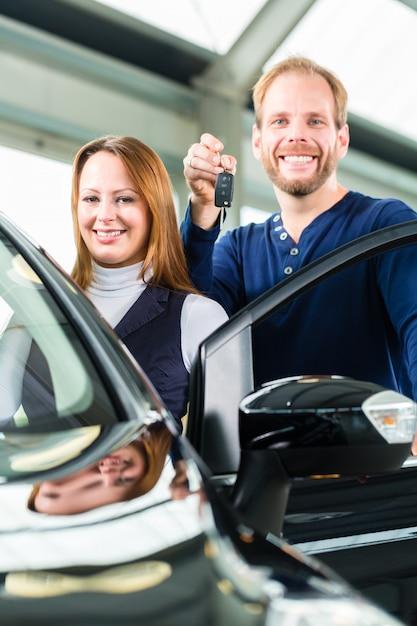 Junger mann mit auto im autohaus Premium Fotos