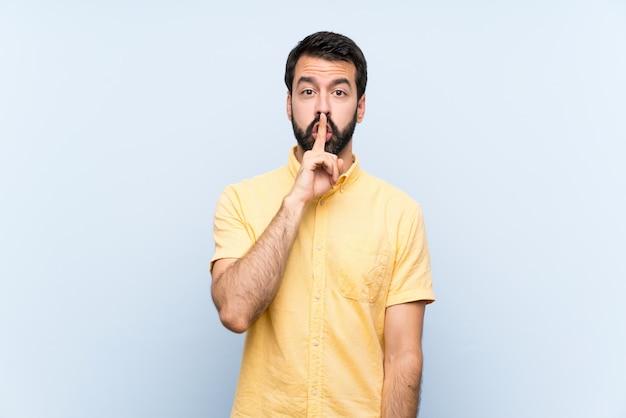 Junger mann mit bart auf dem blau, das ein zeichen der ruhegeste einsetzt finger in mund zeigt Premium Fotos