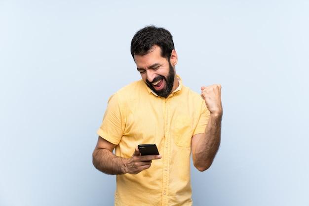 Junger mann mit bart über getrenntem blau mit telefon in siegstellung Premium Fotos