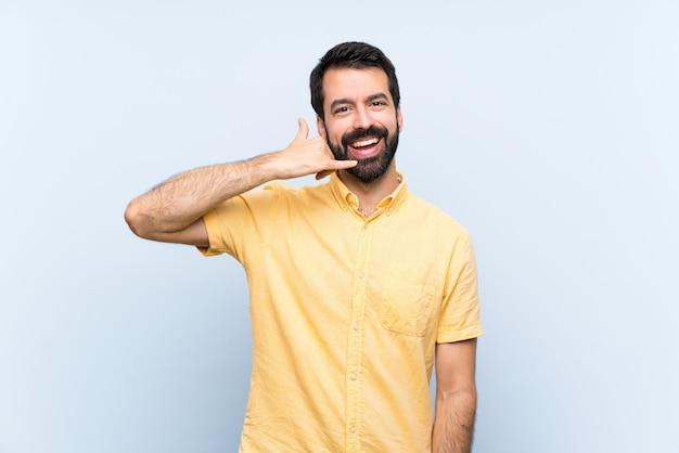 Junger mann mit bart über lokalisiertem blau, das telefongeste macht. rufen sie mich zurück zu unterzeichnen Premium Fotos