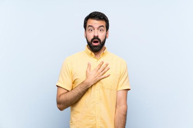 Junger mann mit bart über lokalisiertem blauem hintergrund beim schauen überrascht und entsetzt recht Premium Fotos