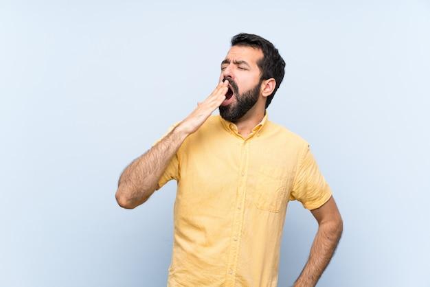 Junger mann mit bart über lokalisierter blauer wand, die weit offenen mund mit der hand gähnt und bedeckt Premium Fotos