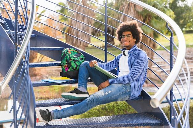 Junger mann mit buch und taschen, die auf dem blauen treppenhaus im park sich entspannen Kostenlose Fotos