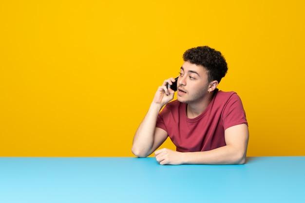 Junger mann mit bunter wand und tabelle, die ein gespräch mit dem handy hält Premium Fotos