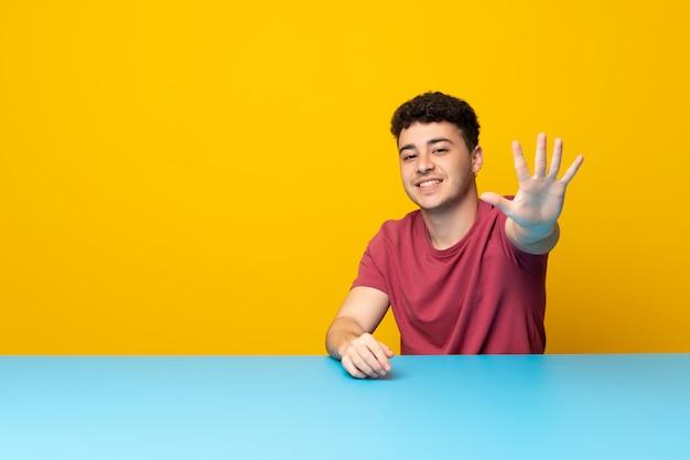 Junger mann mit bunter wand und tabelle, die fünf mit den fingern zählt Premium Fotos