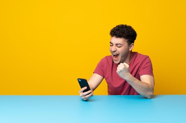 Junger mann mit bunter wand und tabelle mit telefon in siegposition Premium Fotos