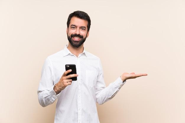 Junger mann mit dem bart, der ein bewegliches haltenes copyspace eingebildet auf der palme hält, um eine anzeige einzufügen Premium Fotos