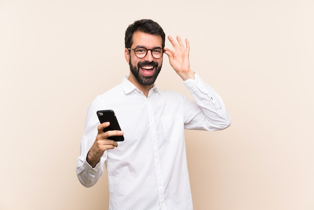 Junger mann mit dem bart, der ein mobile mit gläsern und glücklich hält Premium Fotos