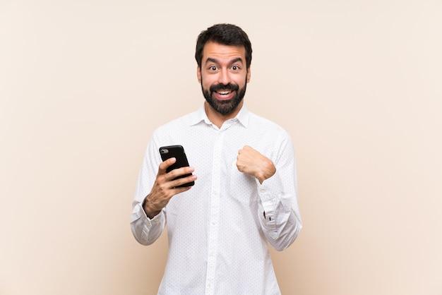 Junger mann mit dem bart, der ein mobile mit überraschungsgesichtsausdruck hält Premium Fotos