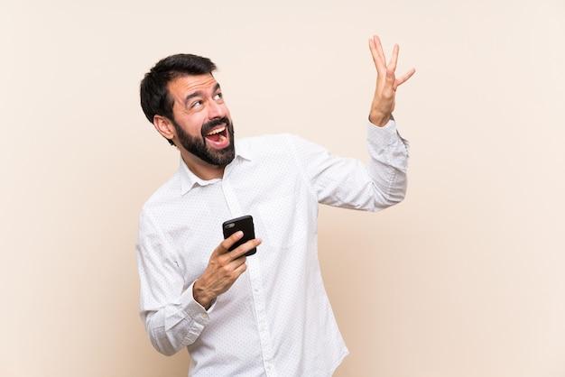 Junger mann mit dem bart, der ein mobile nervös und erschrocken hält Premium Fotos