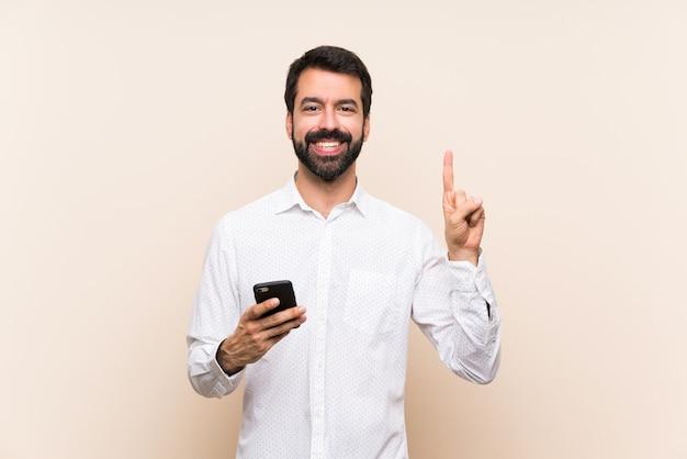 Junger mann mit dem bart, der ein mobile zeigt und einen finger im zeichen des besten anhebt Premium Fotos