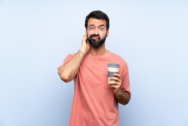 Junger mann mit dem bart, der einen mitnehmerkaffee auf dem blau hat zweifel hält Premium Fotos