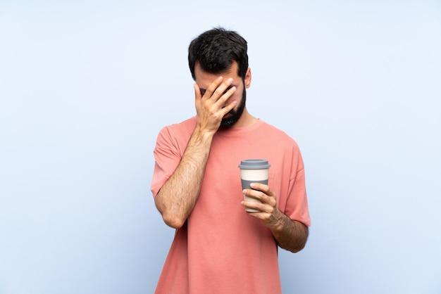 Junger mann mit dem bart, der einen mitnehmerkaffee über getrenntem blau mit müdem und krankem ausdruck anhält Premium Fotos