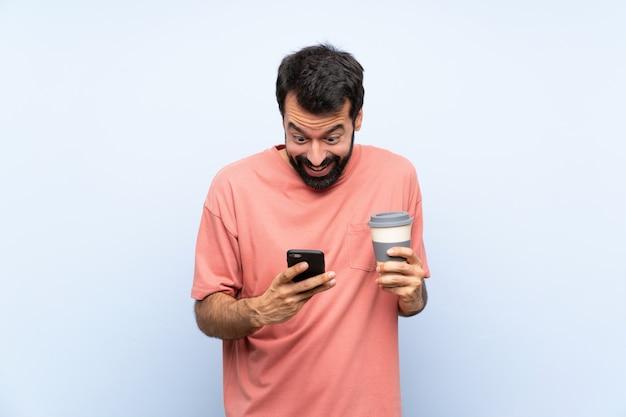Junger mann mit dem bart, der einen mitnehmerkaffee über lokalisiertem blau hält, überraschte und eine mitteilung sendend Premium Fotos