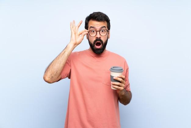 Junger mann mit dem bart, der einen mitnehmerkaffee über lokalisiertem blau mit gläsern und überrascht hält Premium Fotos