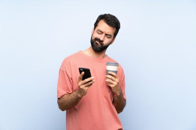 Junger mann mit dem bart, der einen mitnehmerkaffee über lokalisierter blauer wand denkt und sendet eine mitteilung hält Premium Fotos