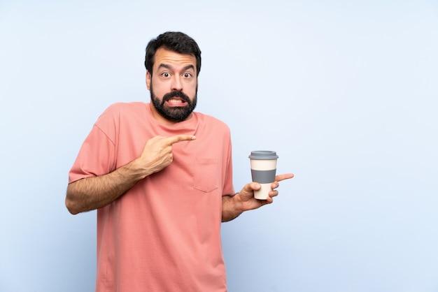 Junger mann mit dem bart, der einen mitnehmerkaffee über lokalisierter blauer wand hält, erschrak und zeigte auf die seite Premium Fotos