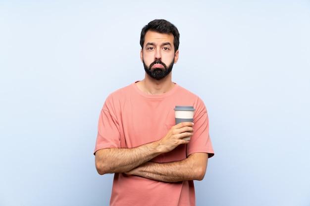 Junger mann mit dem bart, der einen mitnehmerkaffee über lokalisierter blauer wand mit traurigem und deprimiertem ausdruck hält Premium Fotos