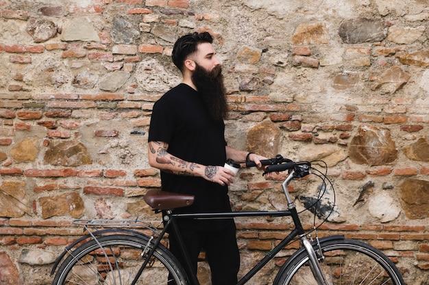 Junger mann mit dem fahrrad, welches die wegwerfkaffeetasse in der hand steht nahe der verwitterten wand hält Kostenlose Fotos