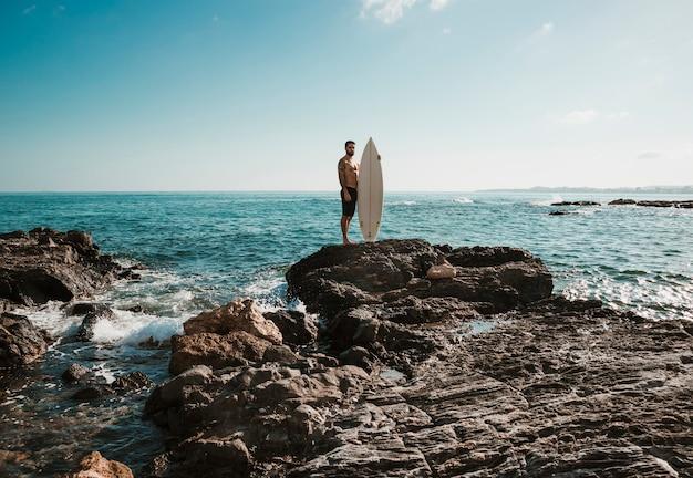 Junger mann mit dem surfbrett nahe, meer spritzend Kostenlose Fotos