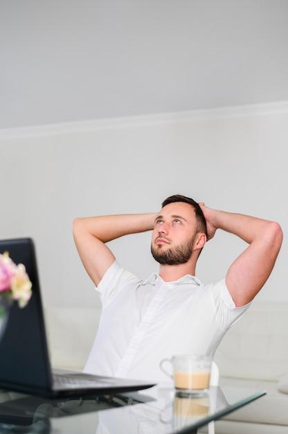 Junger mann mit den händen auf dem kopf, der oben schaut Kostenlose Fotos