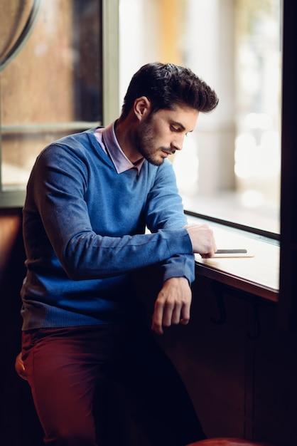 Junger mann mit der blauen strickjacke, die seinen smartphone in einer modernen kneipe betrachtet. Premium Fotos